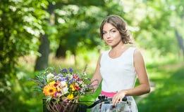 Piękna dziewczyna jest ubranym ładną biel suknię ma zabawę w parku z bicyklem Zdrowy plenerowy stylu życia pojęcie Rocznik scener Obrazy Royalty Free