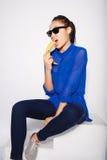 Piękna dziewczyna jest ubranym szkło z bananem w ręce na białym tle Obraz Stock