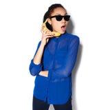 Piękna dziewczyna jest ubranym szkło z bananem w ręce na białym tle Fotografia Stock