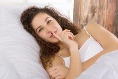 Piękna dziewczyna kłama w łóżkowy samotnym Gest cisza zdjęcie stock
