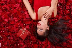 Piękna dziewczyna kłama w płatkach blisko prezenta pudełka, chwyt ręki i spojrzeń, blisko twarzy daleko od obrazy stock