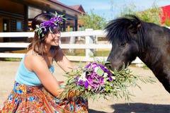 Piękna dziewczyna karmi słomianego konika na gospodarstwie rolnym obraz royalty free
