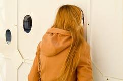 Piękna dziewczyna, kobieta w brązu żakiecie, wtykającym jej głowa w fotografii dziurze w fotografii tle widok z powrotem obrazy stock