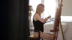 Piękna dziewczyna koncentruje farby obrazek zbiory wideo