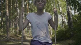 Piękna dziewczyna na huśtawce w lasowej młodej kobiecie jedzie huśtawkę w lesie zbiory