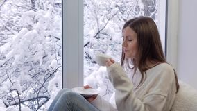 Piękna dziewczyna na siedzącym windowsill, pić kawowym i patrzeć okno, na zewnątrz zimy zbiory wideo