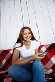 Piękna dziewczyna ogląda tv, ono uśmiecha się, siedzący na kanapie w domu zdjęcie stock