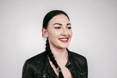 Piękna dziewczyna ono uśmiecha się w czarnej kurtce odizolowywającej z pigtail zdjęcie royalty free