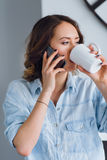 Piękna dziewczyna opowiada na telefonie komórkowym i pije herbaty Obraz Stock