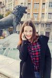 Piękna dziewczyna opowiada na telefonie komórkowym w miastowym mieście Zdjęcie Royalty Free