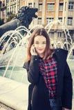 Piękna dziewczyna opowiada na telefonie komórkowym w miastowym mieście Zdjęcia Stock