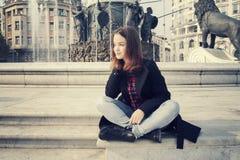 Piękna dziewczyna opowiada na telefonie komórkowym w miastowym mieście Fotografia Stock