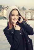 Piękna dziewczyna opowiada na telefonie komórkowym w miastowym mieście Obrazy Royalty Free
