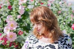 Piękna dziewczyna otaczająca kolorowym kwiatu ślazem Zdjęcia Royalty Free