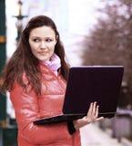 Piękna dziewczyna patrzeje daleko od w parku z laptopem obraz royalty free