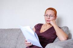 Piękna dziewczyna patrzeje przez podatków dokumentów z szkłami Emocja koncentracja Poważni przepisy obraz royalty free