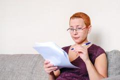 Piękna dziewczyna patrzeje przez podatków dokumentów z szkłami Emocja koncentracja Poważni przepisy zdjęcie royalty free