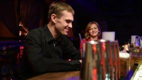 Piękna dziewczyna patrzeje przystojnego młodego faceta w barze zbiory