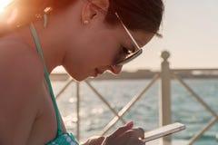 Piękna dziewczyna patrzeje telefon przy morzem jest ubranym okulary przeciwsłonecznych, w kostiumu kąpielowym, tło denna błękitne Zdjęcia Royalty Free