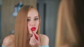 Piękna dziewczyna patrzeje w farbach i lustrze jej wargi z muśnięciem zbiory