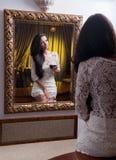 Piękna dziewczyna patrzeje w lustro w krótkiej biel sukni Obraz Royalty Free