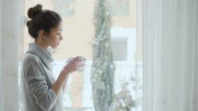 Piękna dziewczyna pije kawę blisko okno przy zimą zdjęcie wideo
