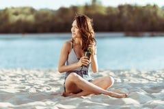 Piękna dziewczyna pije piwo podczas gdy siedzący na piaskowatej plaży i patrzejący daleko od Zdjęcia Royalty Free