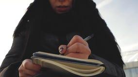 Piękna dziewczyna pisze w notatnika włosy rozwija w wiatrze zbiory