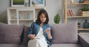 Piękna dziewczyna pisze w notatniku patrzeje smartphone ekran siedzi w domu zbiory