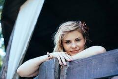 Piękna dziewczyna podpiera up na drewnianym poręczu Zdjęcia Royalty Free