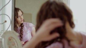Piękna dziewczyna podsyca twój włosy przed lustrem zbiory
