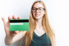 Piękna dziewczyna pokazuje bank kartę, zamazany tło, biały tło, reklamowa karta Obraz Stock