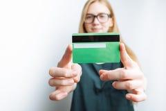Piękna dziewczyna pokazuje bank kartę, zamazany tło, biały tło, reklamowa karta Fotografia Stock