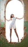 Piękna dziewczyna pozuje modę w nadokiennej ramie Fotografia Royalty Free