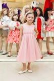Piękna dziewczyna próbuje na różowej sukni w sklepie fotografia stock