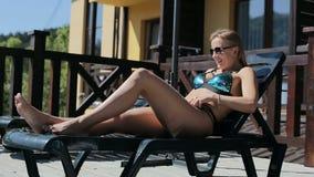 Piękna dziewczyna relaksuje na lounger blisko basenu zdjęcie wideo