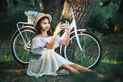 Piękna dziewczyna robi fotografii na telefonie bardzo skupia się zdjęcie stock