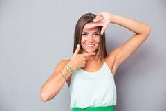 Piękna dziewczyna robi ramowemu gestowi z palcami Obraz Stock