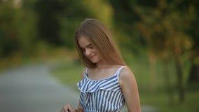 Piękna dziewczyna rysuje obrazek w parku używać paletę z farbami i szpachelką Sztaluga i kanwa z obrazkiem zdjęcie wideo