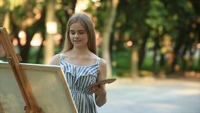 Piękna dziewczyna rysuje obrazek w parku używać paletę z farbami i szpachelką Sztaluga i kanwa z obrazkiem zbiory wideo