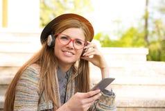 Piękna dziewczyna słucha muzyka na mądrze telefonu obsiadaniu na schodkach w miastowym parku fotografia royalty free