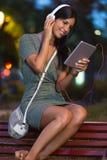 Piękna dziewczyna słucha muzyka w mieście przy nocą zdjęcie royalty free