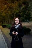 Piękna dziewczyna słucha muzyka w parku Obrazy Royalty Free