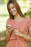 Piękna dziewczyna słucha muzyka z białym telefonem podczas gdy w lato lesie Zdjęcia Stock