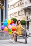 Piękna dziewczyna siedzi na banku w mieście z ballons w ręce zdjęcie royalty free