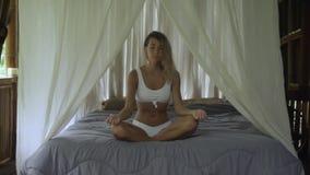 Piękna dziewczyna siedzi w lotosowej pozie, wielki model medytuje na wielkim łóżku z białym baldachimem w tropikalnym hotelu, dni zdjęcie wideo