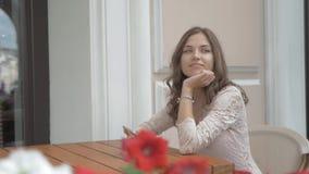 Piękna dziewczyna siedzi w ulicznej kawiarni, używa smartphone i ono uśmiecha się, dobry humor zdjęcie wideo