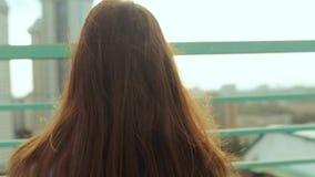 Piękna dziewczyna spotyka świt przeciw tłu miasto krajobraz Młodej dziewczyny stojaki na dachu dom zbiory wideo