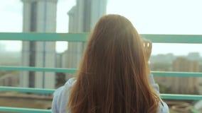 Piękna dziewczyna spotyka świt przeciw tłu miasto krajobraz Młodej dziewczyny stojaki na dachu dom zbiory