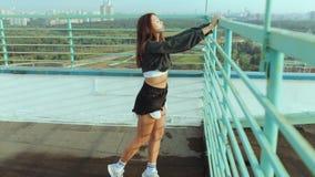 Piękna dziewczyna spotyka świt przeciw tłu miasto krajobraz Młodej dziewczyny stojaki na dachu dom zdjęcie wideo